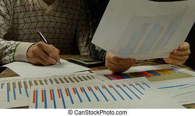 Young businessman and businesswoman analyzing graphs, making calculations and taking notes