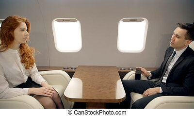 Young businessman and businesswoman are talking, sitting in airplane interior during flight.