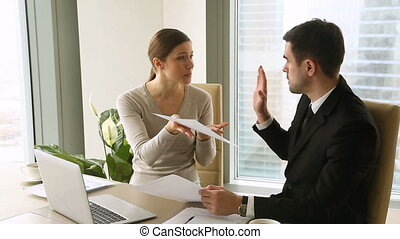 Young businessman and businesswoman arguing at workplace about paperwork error