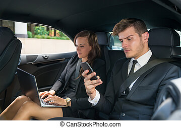 Young Businessman And Businesswoman Traveling In The Car