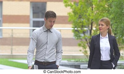 young businessman and businesswoman walking on the street of an business center, slow motion