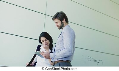 Young businessman and businesswoman with tablet outside in city, talking.