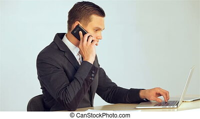 Young businessman answers the call then puts a mobile phone...