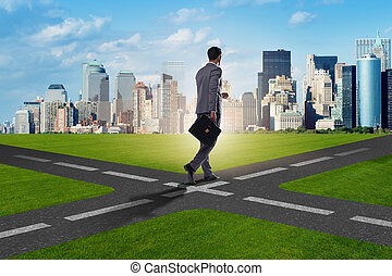 Young businessman at crossroads in uncertainty concept