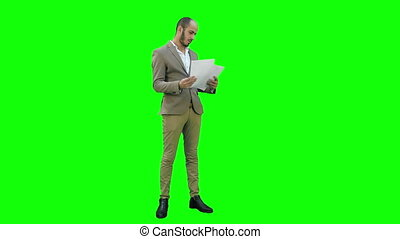 Young businessman attentively studying documents on a Green Screen, Chroma Key.