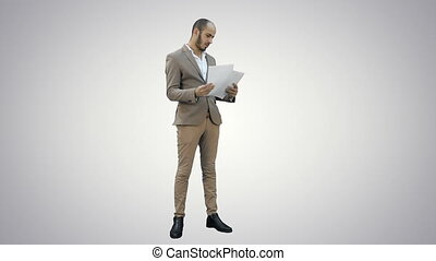 Young businessman attentively studying documents on white background.
