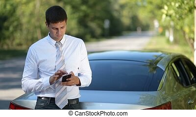 Young businessman browsing net with phone outdoors