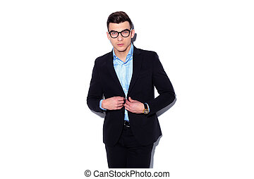 young businessman buttonig his suit