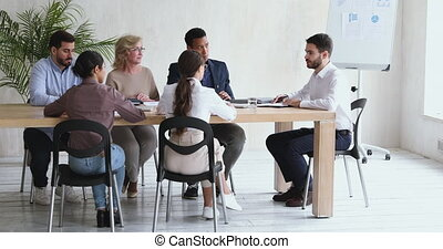 Young businessman ceo executive leading corporate meeting in modern office speaking to diverse staff people instructing workers review work results and planning project during company group briefing