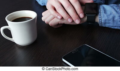 Young businessman checking wrist smart watch - Young man...