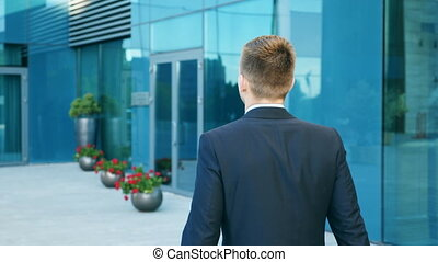 Young businessman commuting to work. Confident guy in suit being on his way to office. Business man with a briefcase walking in city street near modern building. Slow motion Rear back view Close up