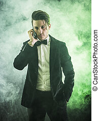 Young businessman confidently posing on dark background