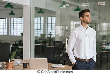 Young businessman deep in thought while standing in an office