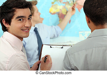 Young businessman discussing a map