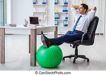 Young businessman doing sports stretching at workplace