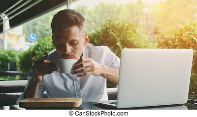 Young businessman dressed in business and glasses sitting in a cafe