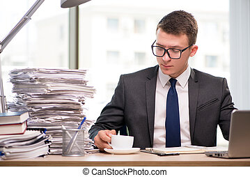Young businessman drinking tea in the office