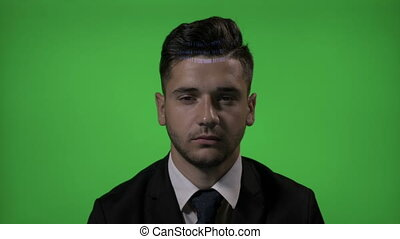 Young businessman entrepreneur working in IT industry having a hologram programming code on face on a green screen background