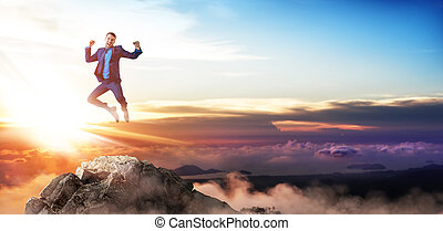 Young businessman feels success and jumps up over mountains