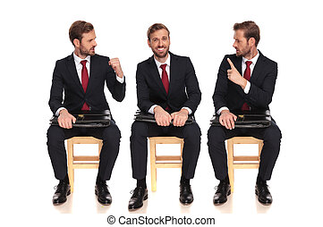 young businessman fighting with himself while sitting