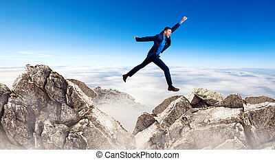 Young businessman flying through the gap among mountains.