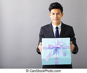 young businessman giving the gift box