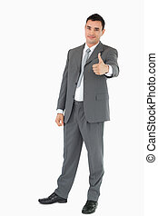 Young businessman giving thumb up