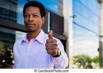 Young businessman giving thumb up.