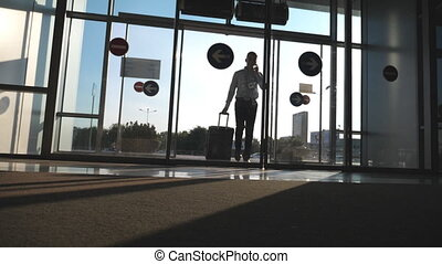 Young businessman going to the airport with his luggage and talking on phone. Man walking with suitcase. Guy goes through glass door and roll suitcase on wheels. Trip or travel concept. Slow motion