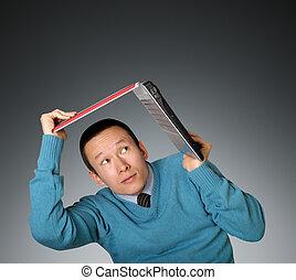 young businessman hides under the laptop