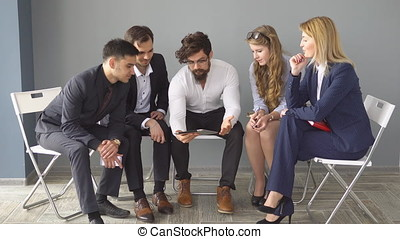 young businessman hipster holds a tablet PC. young entrepreneurs discuss start-up in an empty office