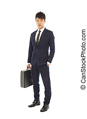 young businessman holding a briefcase and hand in his pocket