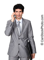 young businessman holding a briefcase and talking on his cell