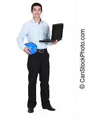 young businessman holding a helmet and a laptop