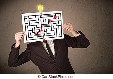 Young businessman holding a paper with a labyrinth on it in front of his head