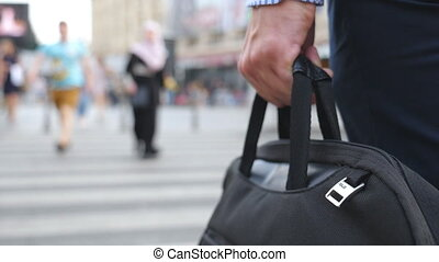 Young businessman holding bag in hand and crossing the road in downtown. Unrecognizable male entrepreneur carry briefcase in arm and walking a crosswalk in big city. Rear view Slow motion Close up