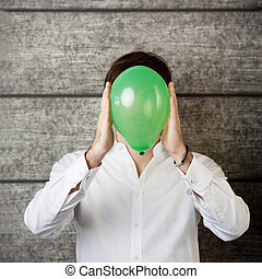 Young businessman holding balloon in front of face while standing against wooden wall