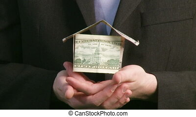 Businessman holding house of Dollars
