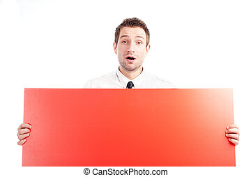 Young businessman holding red blank sign surprised