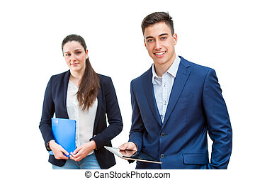 Young businessman holding tablet with female partner in background.