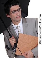 young businessman holding umbrella