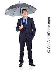 young businessman holding umbrella