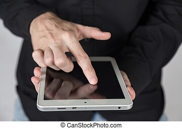 Young businessman holds tablet.