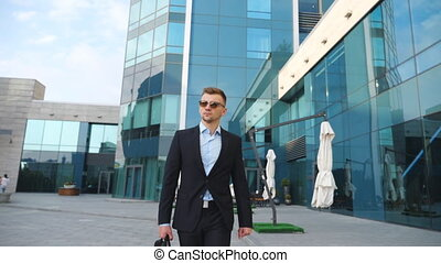 Young businessman in a black suit with briefcase walking along modern office building. Confident male entrepreneur with bag goes to job. Handsome guy commuting to work. Slow motion Close up