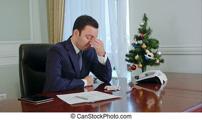 Young businessman in a suit rubs his nose, looking down have no idea and tired. We understand from his face that he was very upset and tired