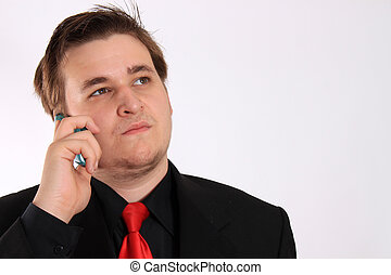 Young businessman in black formal suit talking on cellphone