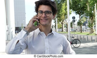 Young businessman in city talking on cell phone