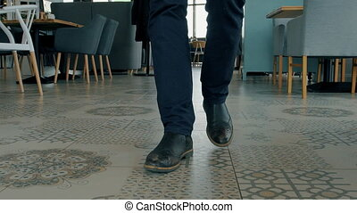 Young businessman in formal attire and shoes is walking...