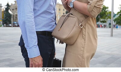 Young businessman in formal wear with briefcase and businesswoman in dress standing at city street. Business couple meeting in urban environment. Side view Close up Slow motion Crane shot