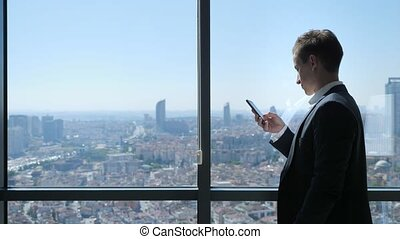 Young businessman in office is browsing phone near the window with panoramic city view.